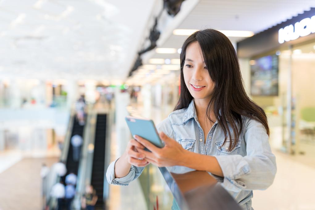 Frau mit Smartphone in einem Einkaufszentrum